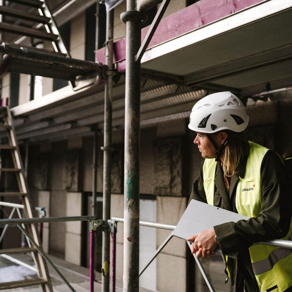 Kvinna mot räcke på byggarbetsplats